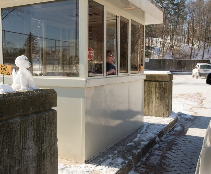 Parking Attendant, Jackie Snow, greets visitors at the booth on Euclid Ave, next to her canine snow sculpture that reads