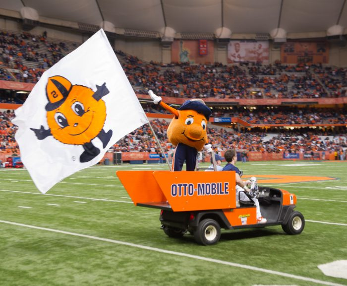 Otto the Orange riding on the back of an orange golf cart labeled as the Otto-Mobile