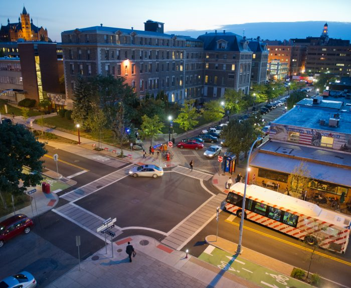 A bus waits to turn onto South Crouse Ave, near Crouse-Hinds Hall on main campus at twilight.