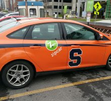 One of the Zipcars in service at Syracuse University has an orange graphic wrap, complete with the Syracuse block