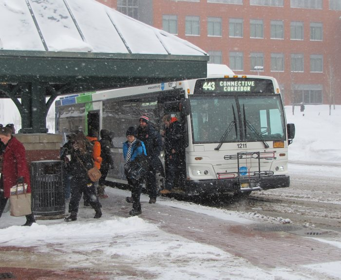 A bus is stopped at College Place, and people exit the open doors.