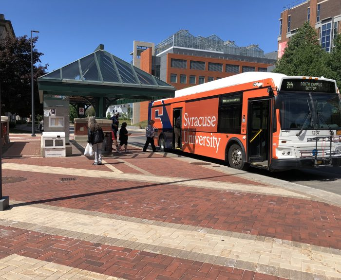 College place bus stop with students getting on Centro bus that is orange with Syracuse University on the side of it.