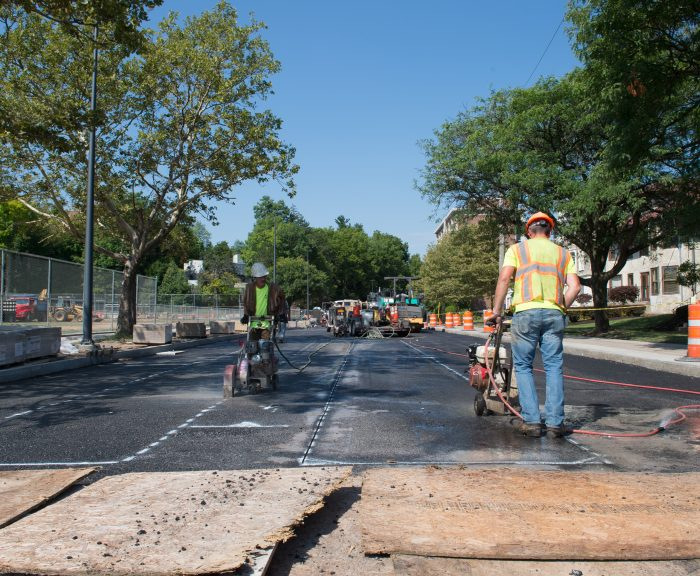 Works preforming road maintenance at the campus entrance on Euclid Avenue.