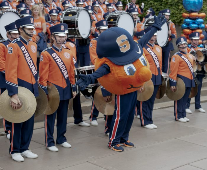 Picture of Otto in front of SU band members holding their instruments.