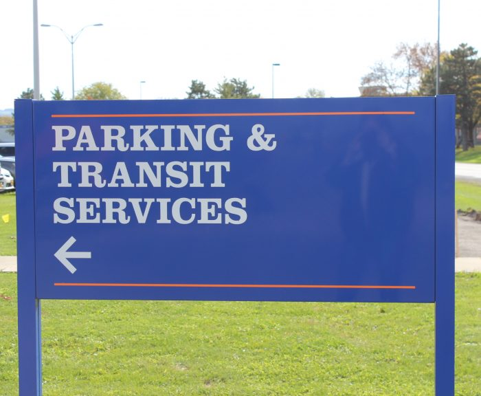 Blue sign that reads parking and transit services