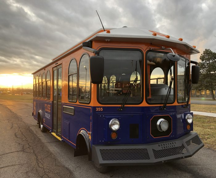Orange and blue trolley parked with the sun coming up in the background