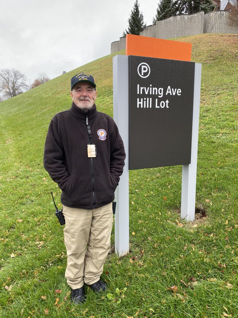 Man Standing Next To Irving Ave. Hill Lot Sign