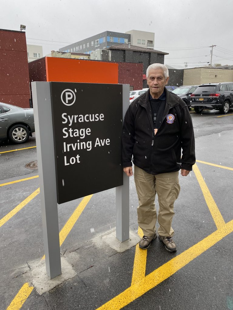 Man Standing Next To Syracuse Stage Irving Ave Lot Sign