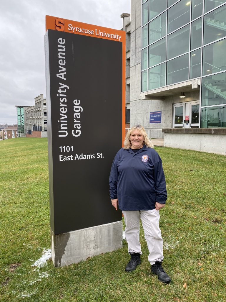 Woman Standing Next To University Ave. Garage Sign