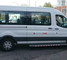 White Passenger Van with Access Cuse signage on it